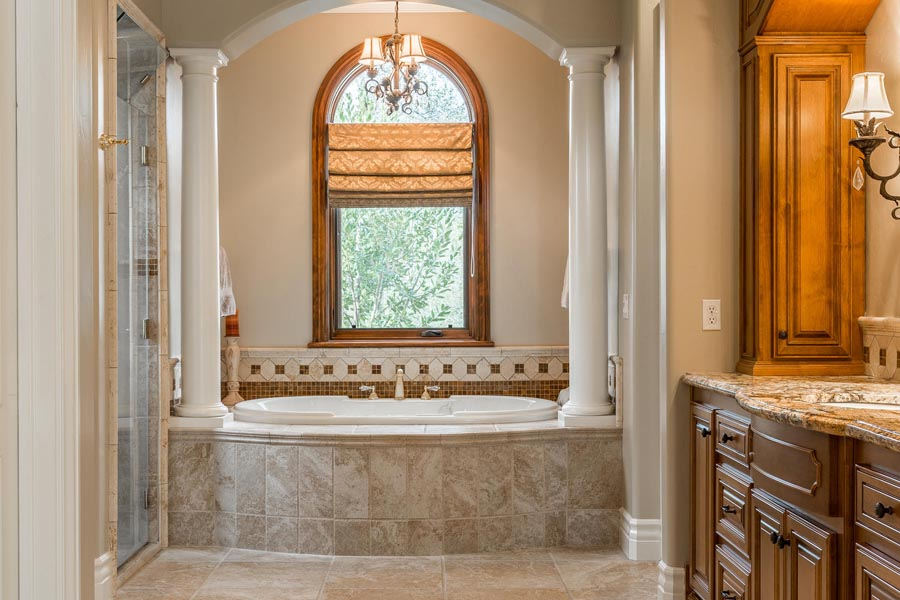 Master bathroom includes jetted tub with views of the oak trees