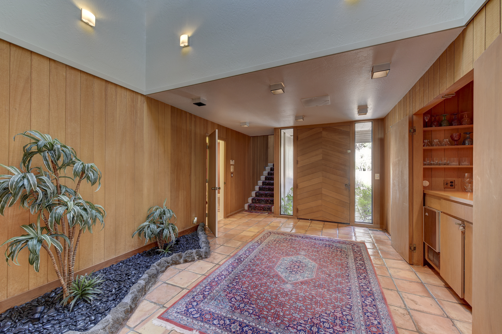 Vintage entry way with wood siding and hidden wetbar in entry way of 3600 Kiekebusch Court