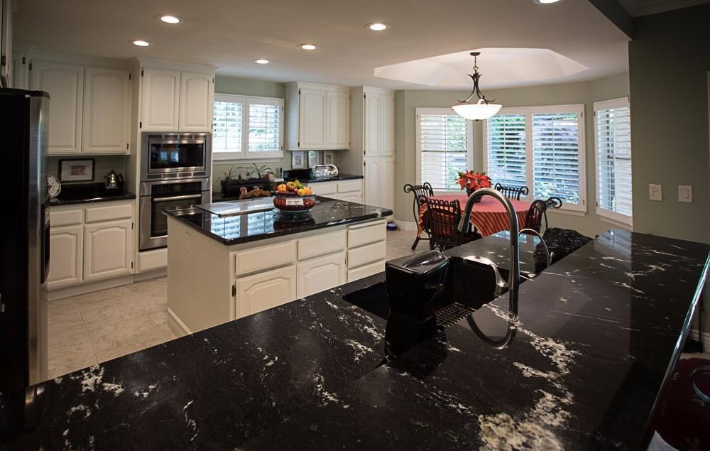Spacious kitchen with black granite counters, white cabinets, large island and breakfast nook