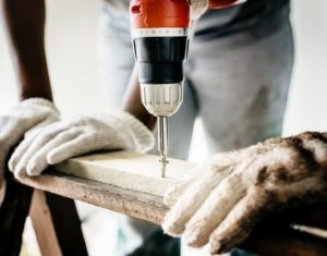 blog post image about winterizing your home showing power drill screwing bolt into wood